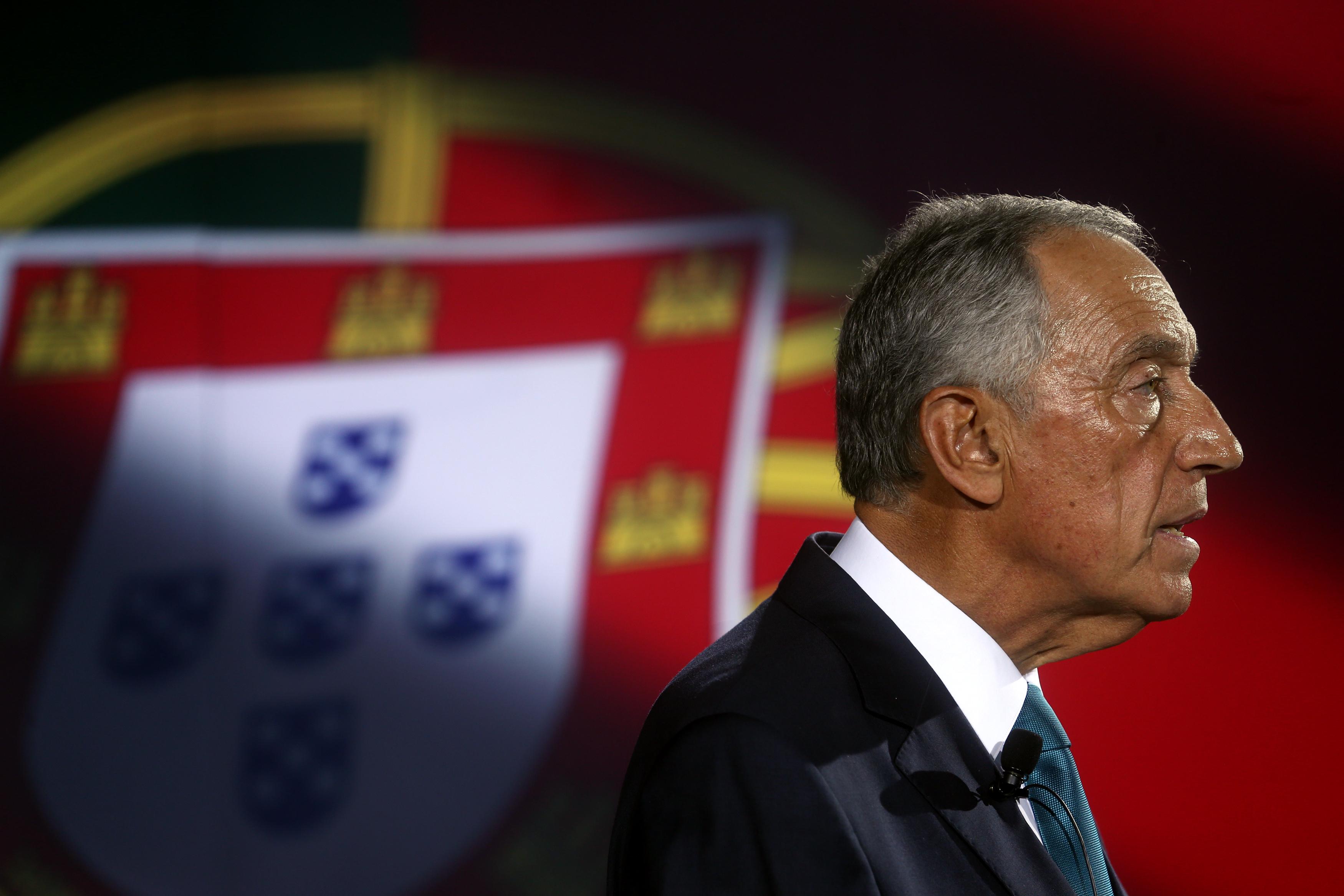 Imagem de Marcelo Rebelo de Sousa de perfil, com bandeira de Portugal como pano de fundo.
