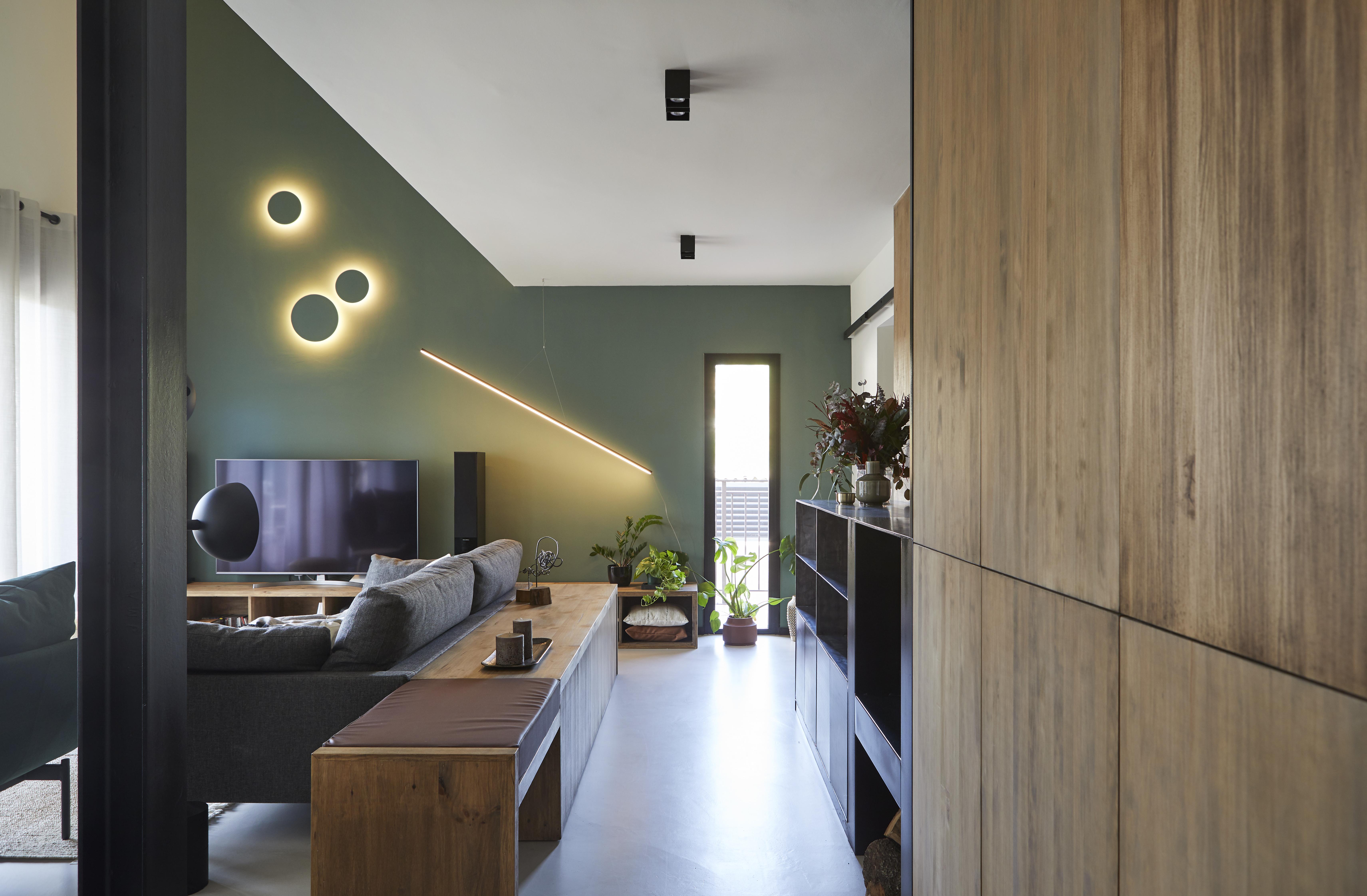 A parede verde destaca-se com a madeira e o preto