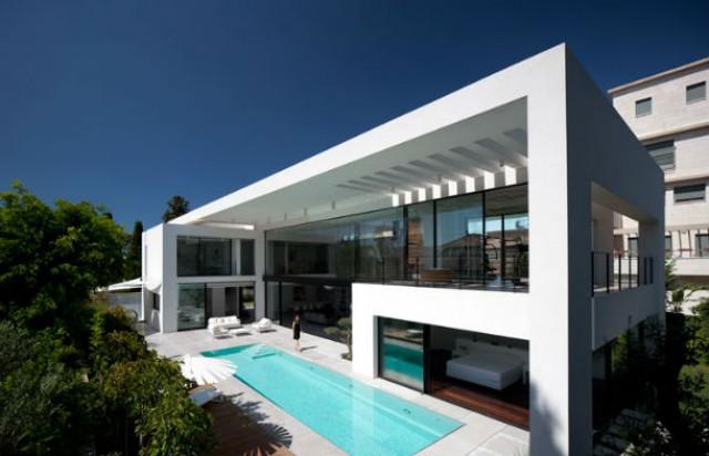 no exterior da casa, ao longo da fachada principal, existe uma piscina